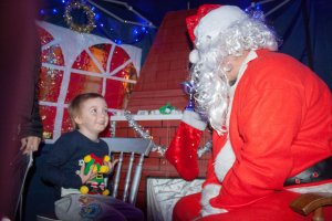 Santa with a young child at his Grotto